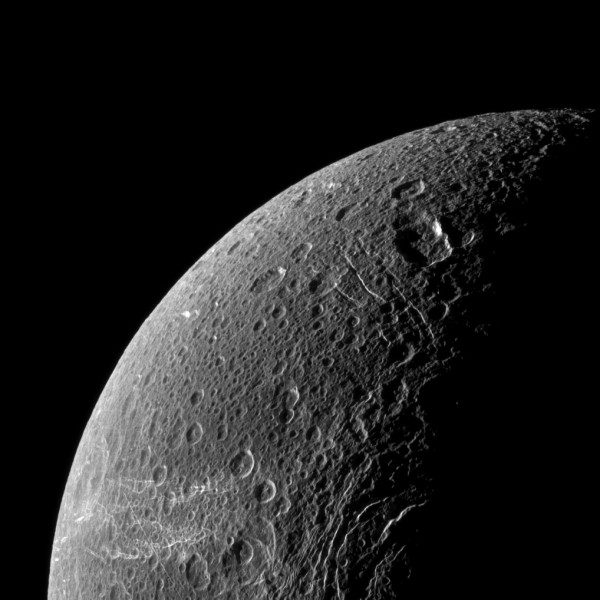 "Angled sunlight brings Dione's ""wispy lines"" into relief"