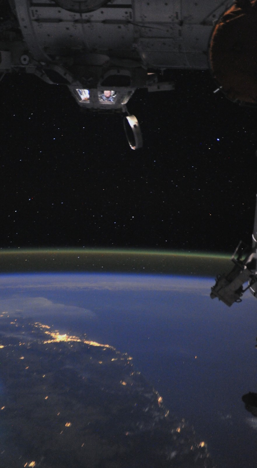 ISS astronaut Ron Garan peers out if the Station's cupola at the Earth below.