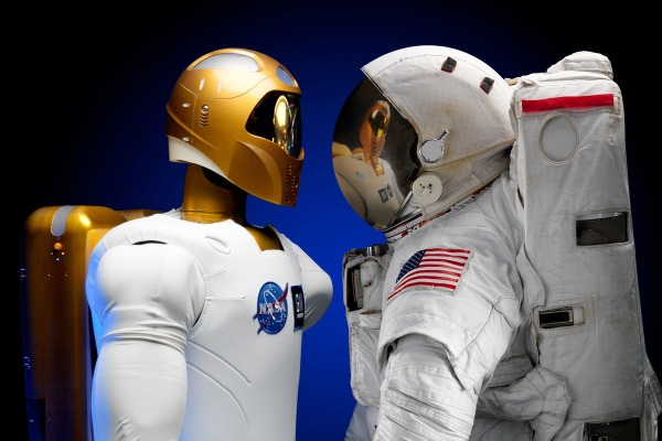 NASA's Robonaut2 faces off with an astronaut in a space suit (NASA/JSC)
