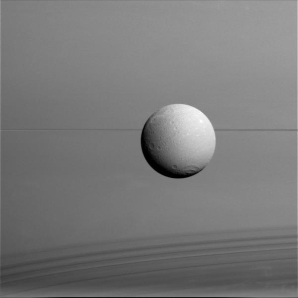 Dione imaged from a distance of 45,000 miles (73,000 km) on Aug. 17, 2015. Saturn fills the background, its edge-on rings cutting a thin dark line across the center with their shadows falling across the planet's clouds at bottom.