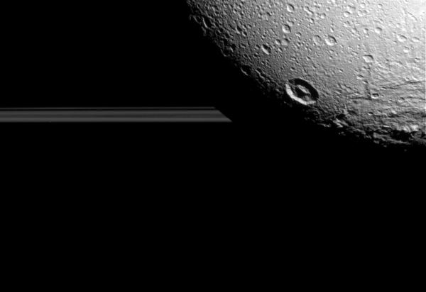 Dione's night side blocks the view of Saturn's rings, seen edge-on as Cassini approached the moon on Aug. 17, 2015.