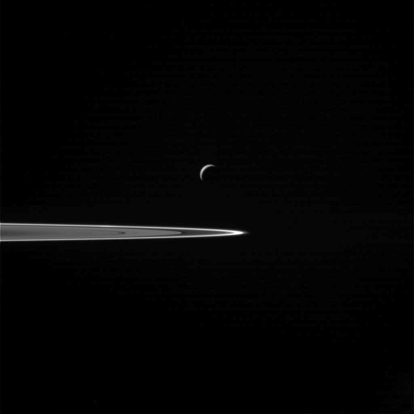 Enceladus seen before the flyby in front of Saturn's rings.