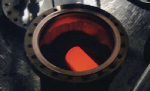 Plutonium dioxide glows with the heat of its natural decay inside a protective cylindrical shell of graphite. (DOE/Idaho National Laboratory)