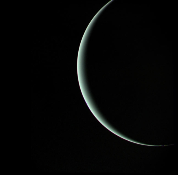 The blue-green crescent of Uranus imaged by a departing Voyager 2 on January 25, 1986 (NASA)